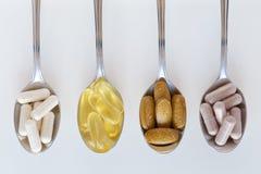 Gezonde supplementen op theelepeltjes stock foto's