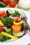 Gezonde veganist die groentenvoedsel op plaat eten Royalty-vrije Stock Afbeeldingen