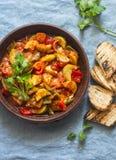Gezonde vegetarische lunch - gestoofde tuingroenten Plantaardige ratatouille en geroosterd brood Op een blauwe achtergrond stock foto