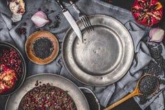 Gezonde vegetarische zwarte linzesalade met granaatappel op keukenlijst met leeg plaat en bestek, hoogste mening Stock Afbeelding