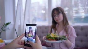 Gezonde voeding en het blogging, vrolijk meisje in oogglazen die met verse vruchten op plaat voor meisje stellen dat foto neemt stock video