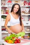 Gezonde voeding en zwangerschap Jongelui die de zwangere groenten van vrouwenbesnoeiingen op salade glimlachen Royalty-vrije Stock Fotografie