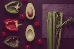 Gezonde voedsel schone het eten selectie op grijze achtergrond Groene en rode groene paprika, avocado, selderie en tomaten Hoogst stock afbeelding