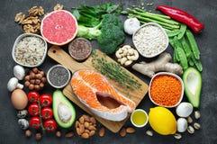 Gezonde voedsel schone het eten selectie: vissen, fruit, noten, groente, zaden, superfood, graangewassen, bladgroente op zwart be stock afbeelding