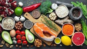 Gezonde voedsel schone het eten selectie: vissen, fruit, noten, groente, zaden, superfood, graangewassen, bladgroente op zwart be stock fotografie