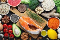 Gezonde voedsel schone het eten selectie: vissen, fruit, noten, groente, zaden, superfood, graangewassen, bladgroente op zwarte stock afbeeldingen