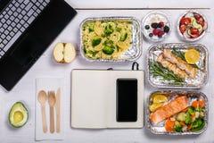 Gezonde voedsellevering aan werkruimte - containers, laptop, mobiele telefoon stock foto