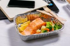 Gezonde voedsellevering aan werkruimte - containers, laptop, mobiele telefoon stock fotografie