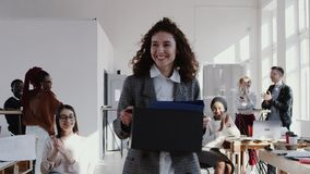 Gezonde werkplaats, gelukkige Kaukasische vrouwelijke manager die nieuw modern die bureau ingaan met een vakje, langzaam motie RO stock videobeelden