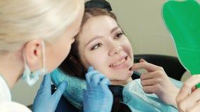 Gezonde witte vrouwentanden en de spiegelclose-up van de tandartsmond stock footage