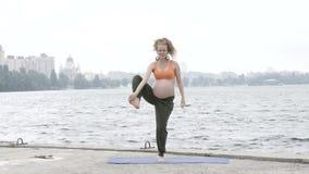 Gezonde zwangere vrouw die yoga in aard in openlucht doen stock videobeelden