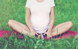 Gezonde zwangere vrouw het praktizeren yoga in aard in openlucht Toekomstig mamma die uitrekkende oefeningen doen Prenatale Yoga  royalty-vrije stock afbeelding