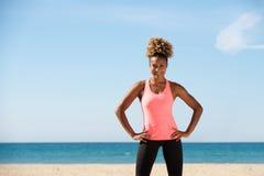 Gezonde zwarte jonge vrouw die zich met handen op heupen bij het strand bevinden royalty-vrije stock fotografie