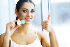 Gezondheid en schoonheid Jonge Vrouw die Contactlenzen toepast Verse Mening Portret van een Mooie Vrouw met Groen Contact stock afbeelding