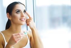 Gezondheid en schoonheid Jonge Vrouw die Contactlenzen toepast Verse Mening Portret van een Mooie Vrouw met Groen Contact stock afbeeldingen