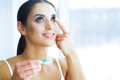 Gezondheid en schoonheid Jonge Vrouw die Contactlenzen toepast Verse Mening Portret van een Mooie Vrouw met Groen Contact stock fotografie