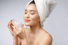 Gezondheid en schoonheidsconcept - Aantrekkelijke Aziatische vrouw die room op haar huid toepassen, die op wit wordt geïsoleerd stock afbeeldingen