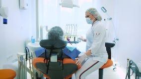 Gezondheid en tandzorg, vrouw aan het werk als tandarts en arts, die aan een mannelijke patiënt spreken Bespreek binnen tandbehan stock footage