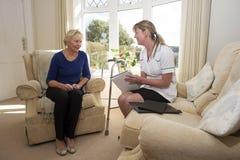 Gezondheidsbezoeker op een huisbezoek met bejaarde dame stock afbeelding