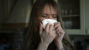 Gezondheidsproblemen voor het jonge vrouw niezen in de keuken stock footage