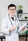 Gezondheidszorg, beroep en geneeskundeconcept - glimlachende mannelijke arts die duimen over medische bureauachtergrond tonen royalty-vrije stock afbeelding
