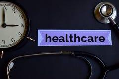 Gezondheidszorg op het drukdocument met de Inspiratie van het Gezondheidszorgconcept wekker, Zwarte stethoscoop stock afbeelding