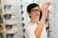 Gezondheidszorg, zicht en visieconcept - gelukkige vrouw die glazen kiezen bij opticaopslag stock foto's