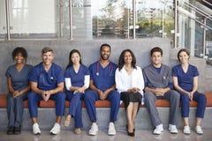 Gezondheidszorgarbeiders die samen in het modern ziekenhuis zitten stock afbeelding