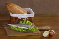 Gezouten haringen, sla, olijven, uien, houten bac van de broodmand Stock Foto