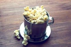 Gezouten popcorn op een houten lijst in een metaalkom Royalty-vrije Stock Foto's
