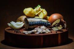 Gezouten vissen met aardappel en ui op houten blok royalty-vrije stock foto's