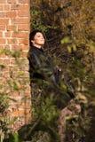 Ggirl heeft tegen een bakstenen muur geleund Royalty-vrije Stock Foto's