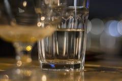 Gglass der halb vollen Stellung des Wassers auf Holztisch Lizenzfreie Stockbilder