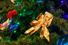 Ggolden bow on an artificial Christmas tree close Royalty Free Stock Image