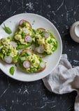 Äggrörasallad med rädisan och gröna ärtor frukosterar rostat bröd på den mörka stenbakgrunden Arkivbild