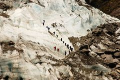 A Gguided group on a glacier. A guided group descends a face of the Franz Joseph glacier in New Zealand stock image