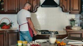 Gguy prende un piatto e lo ha messo sulla tavola, lui aspetta prima che il pancake sia pronto archivi video