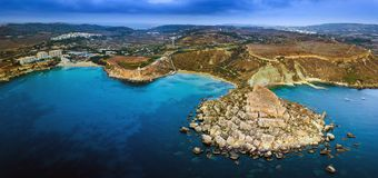 Ghajn Tuffieha, Malta - Aerial panoramic skyline view of the coast of Ghajn Tuffieha with Golden Bay, Riviera Bay. Ghajn Tuffieha Watch Tower and other sandy Stock Photos