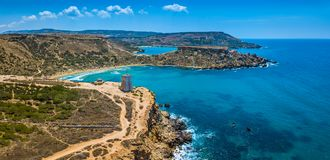 Ghajn Tuffieha, Malta - Aerial panoramic view of the beautiful Ghajn Tuffieha Bay, Ghajn Tuffieha Watch Tower. And Riviera beach on a bright summer day with Royalty Free Stock Images