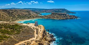 Ghajn Tuffieha, Malta - Aerial panoramic view of the beautiful Ghajn Tuffieha Bay, Ghajn Tuffieha Watch Tower. And Riviera beach on a bright summer day with Stock Images