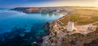 Ghajn Tuffieha, Malta - Aerial panoramic view of the coast of Ghajn Tuffieha with Watch Tower. Golden Bay beach and crystal clear sea water at sunrise Royalty Free Stock Photos