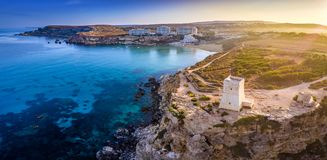 Ghajn Tuffieha, Malta - Aerial panoramic view of the coast of Ghajn Tuffieha with Watch Tower, Golden Bay. Beach and crystal clear sea water at sunrise stock photos
