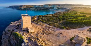 Ghajn Tuffieha, Malta - Aerial panoramic view of Ghajn Tuffieha Watch Tower. With Golden Bay beach and crystal clear sea water at sunrise Royalty Free Stock Photos