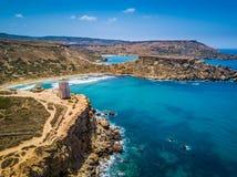 Ghajn Tuffieha, Malta - Beautiful Ghajn Tuffieha Bay, Ghajn Tuffieha Watch Tower and Riviera beach from above. On a bright summer day with Gnejna Bay and blue Royalty Free Stock Photos