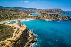 Ghajn Tuffieha, Malta - Beautiful Ghajn Tuffieha Bay, Ghajn Tuffieha Watch Tower and Riviera beach from above. On a bright summer day with Gnejna Bay and blue Royalty Free Stock Photography