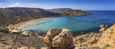 Ghajn Tuffieha, Malta - Beautiful summer day at Ghajn Tuffieha s. Andy beach with blue sky and crystal clear green sea water Stock Image