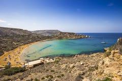 Ghajn Tuffieha, Malta - Beautiful summer day at Ghajn Tuffieha sandy beach with blue sky. And crystal clear green sea water Royalty Free Stock Images