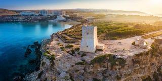 Ghajn Tuffieha, Malta - Beautiful sunrise at Ghajn Tuffieha Watch Tower. With Golden Bay beach at background Stock Image