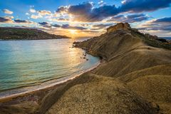 Ghajn Tuffieha, Malta - Beautiful sunset at Ghajn Tuffieha and Gnejna beach on a sunny summer afternoon with colorful clouds Royalty Free Stock Photography