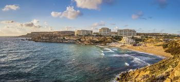 Ghajn Tuffieha, Malta - Panoramic skyline view of Golden Bay, Ma. Lta`s most beautiful sandy beach at sunset with blue sky and clouds Stock Images